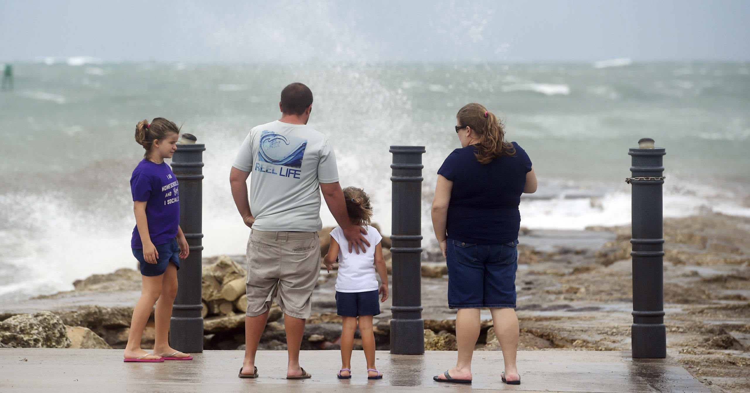 Elizabeth Whittemore (from left), along with her father James, sister Jordan and mother Susan, stand at the end of the South Jetty in Fort Pierce on Aug. 2, 2020, watching the waves crash over the rocks brought by the high winds of Tropical Storm Isaias churning off the coast.
