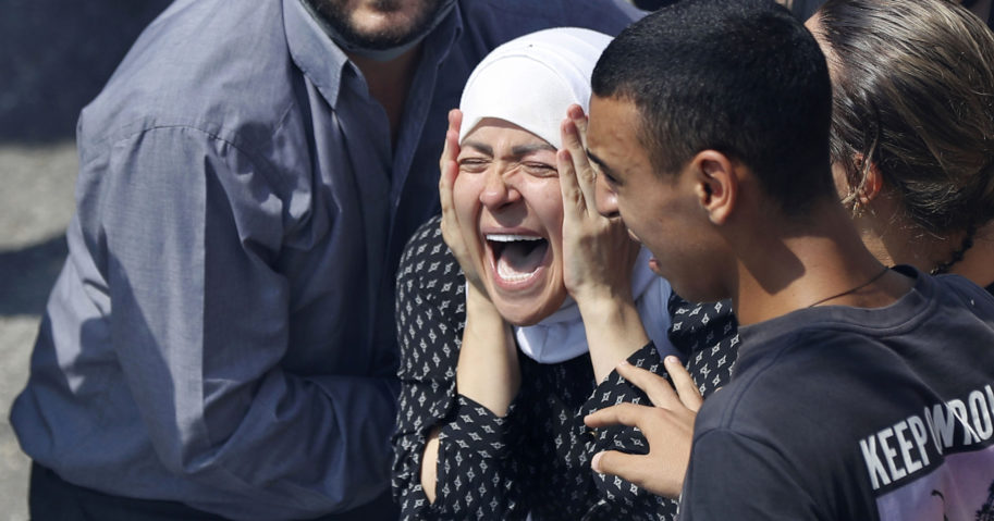 The wife of Rami Kaaki, one of ten firefighters who were killed during last week's explosion at the seaport of Beirut, mourns during her husband's funeral in Beirut, Lebanon, on Aug. 11, 2020.