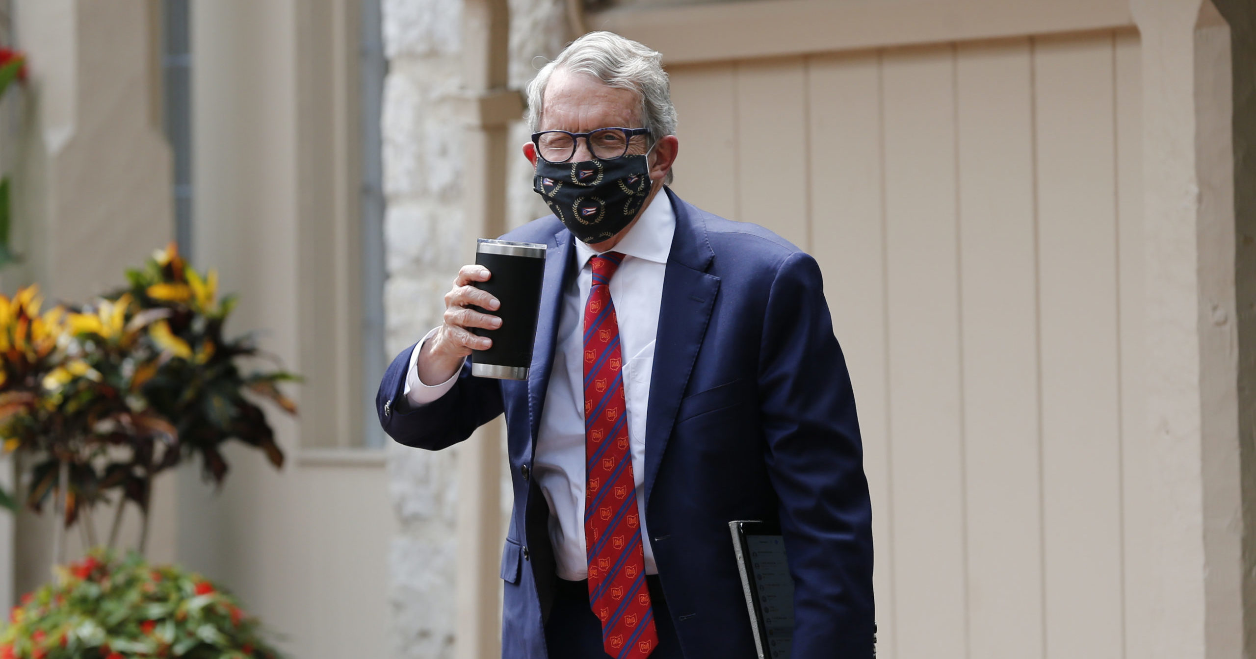 Ohio Gov. Mike DeWine acknowledges members of the media while entering his residence after testing positive for COVID-19 on Aug. 6, 2020, in Bexley, Ohio. DeWine tested negative later in the day using a different test.