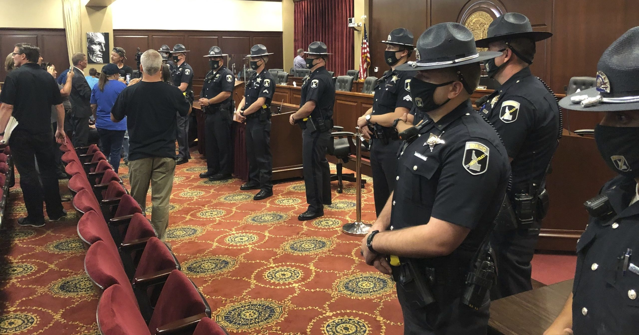 Idaho State Police stand guard in a committee meeting room in the Idaho Statehouse in Boise, Idaho, on Aug. 25, 2020. The committee left the room as a crowd of more than 100 became disruptive.