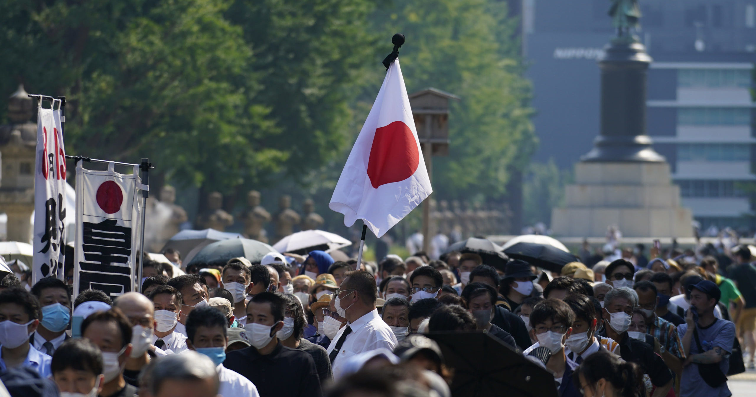 Worshippers queue to pay respects to the war dead at a shrine on Aug. 15, 2020, in Tokyo. Japan marked the 75th anniversary of the end of World War II.