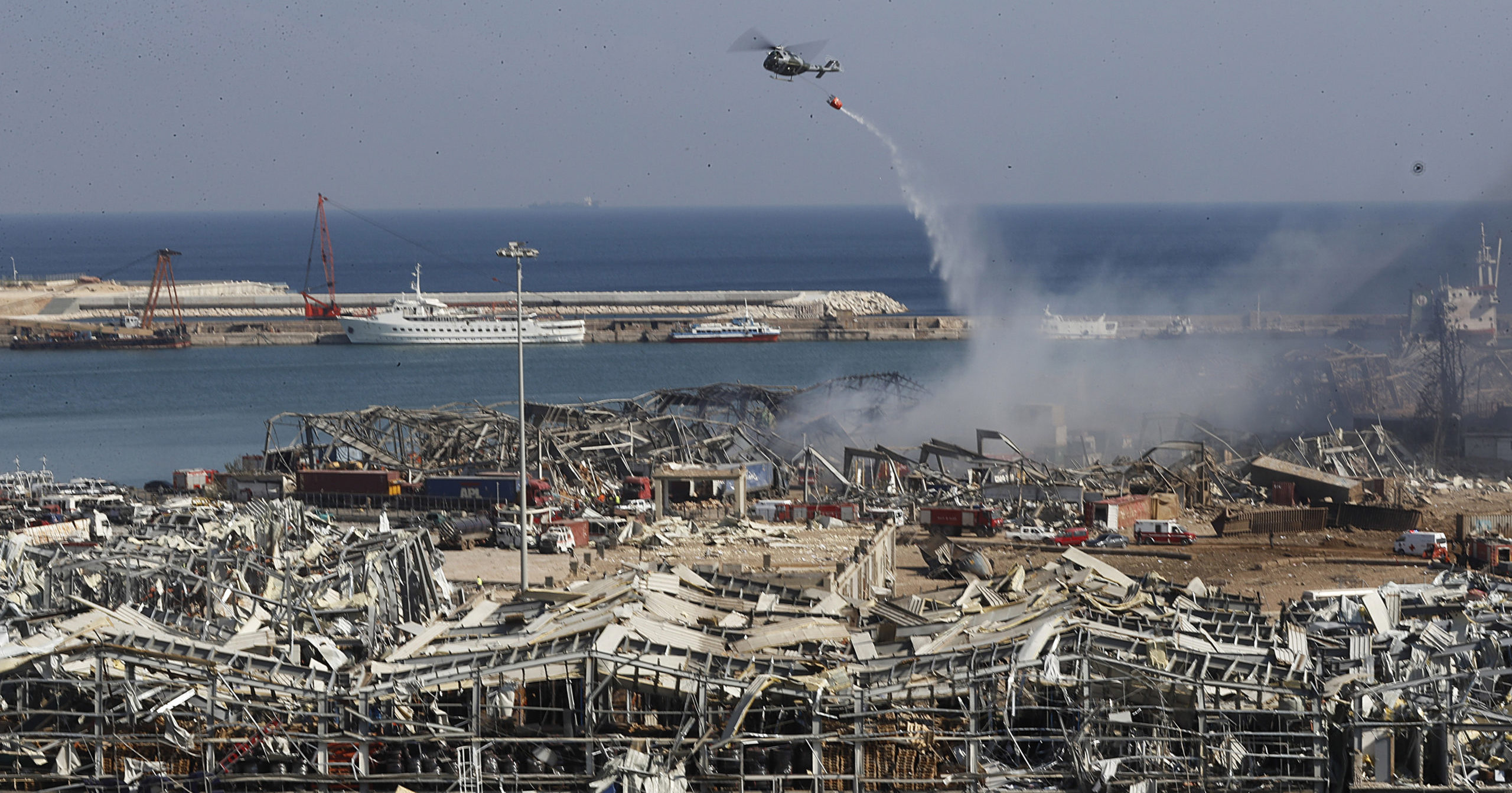 A Lebanese army helicopter dumps water at the scene where an explosion hit the seaport of Beirut, Lebanon, on Aug. 5, 2020, killing at least 100 people and wounding thousands.