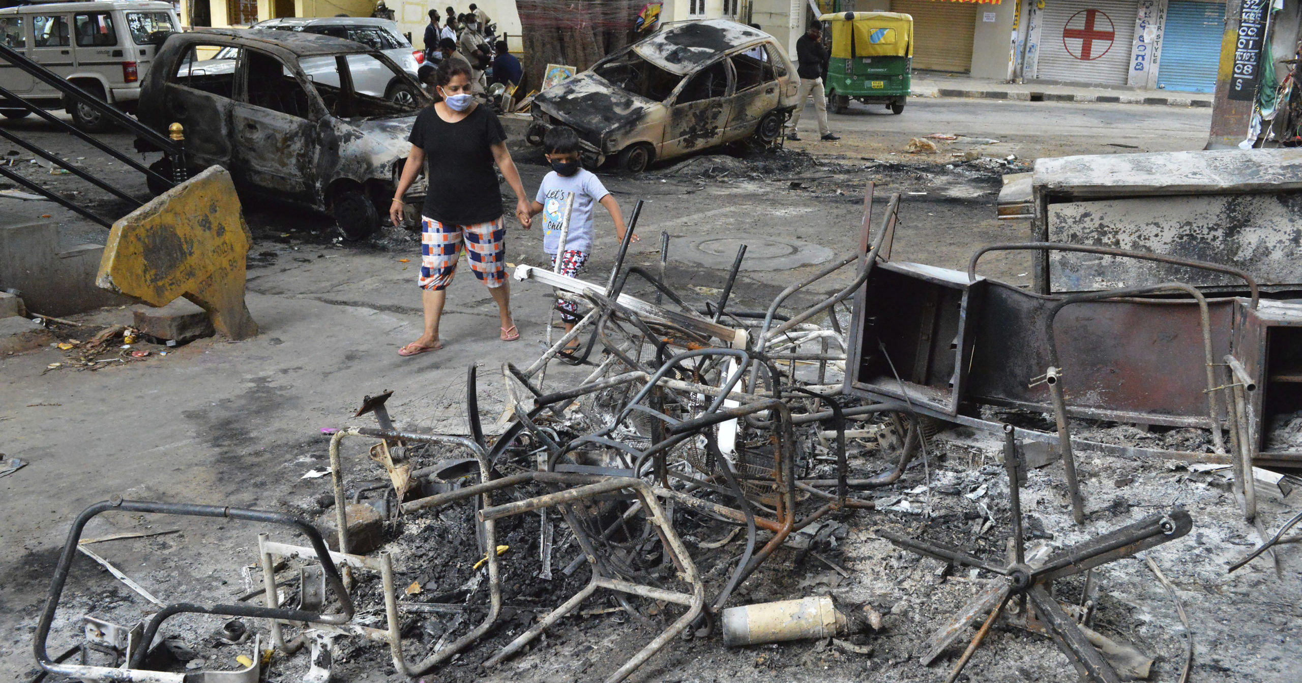 A woman and a child walks past the wreckage of vehicles and furniture burnt during violent protests in Bengaluru, India, on Aug. 12, 2020. At least three people have died in the southern Indian city also known as Bangalore after hundreds of demonstrators clashed with the police overnight against a Facebook post considered offensive to Muslims, attacking a police station and setting fire to vehicles, police said.