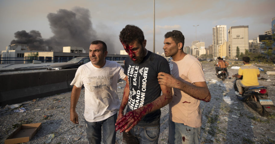 People help a man wounded in a massive explosion in Beirut, Lebanon, on Aug. 4, 2020.