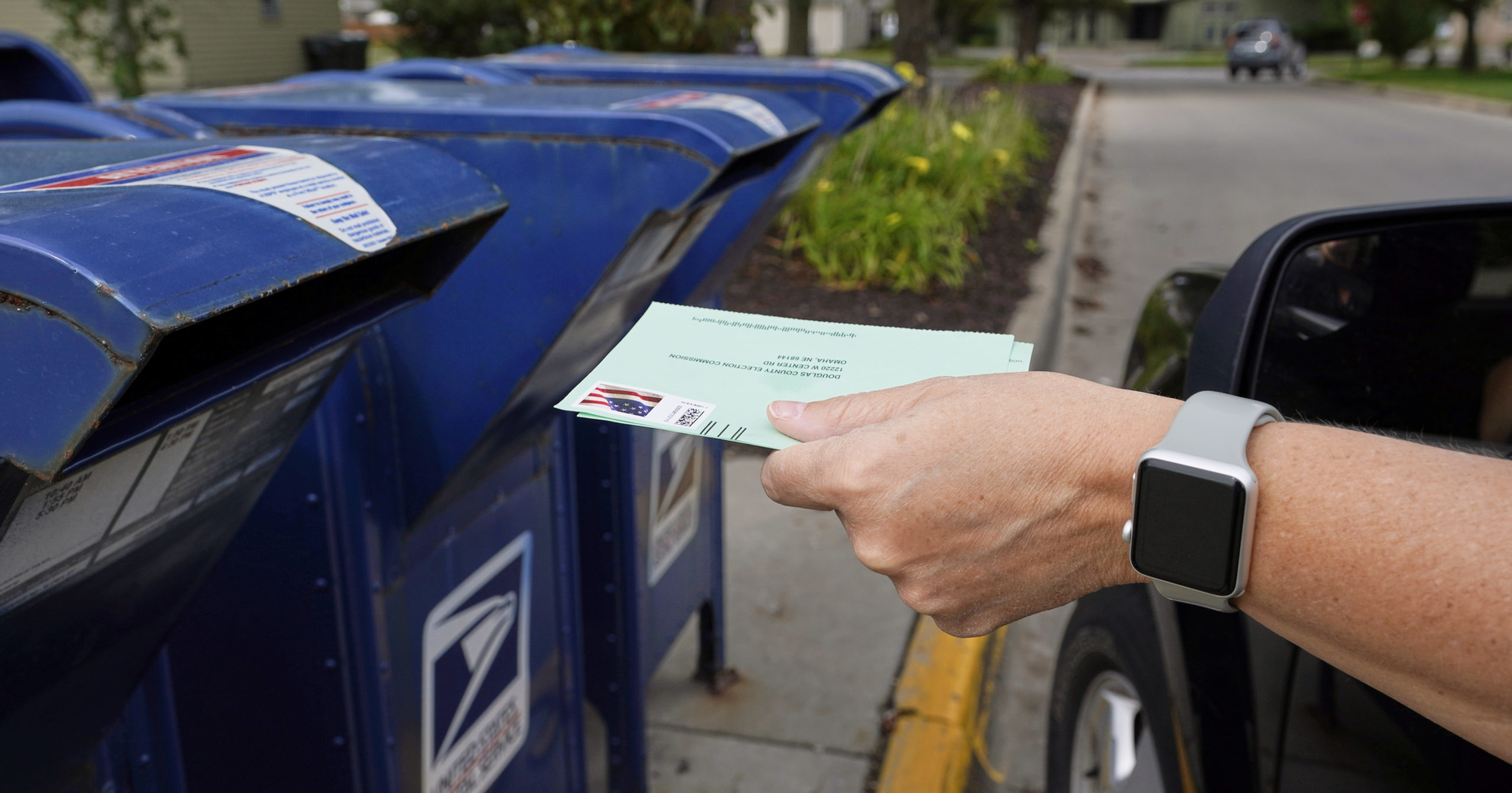 In this Aug. 18, 2020, file photo, a person drops applications for mail-in ballots into a mailbox in Omaha, Nebraska.