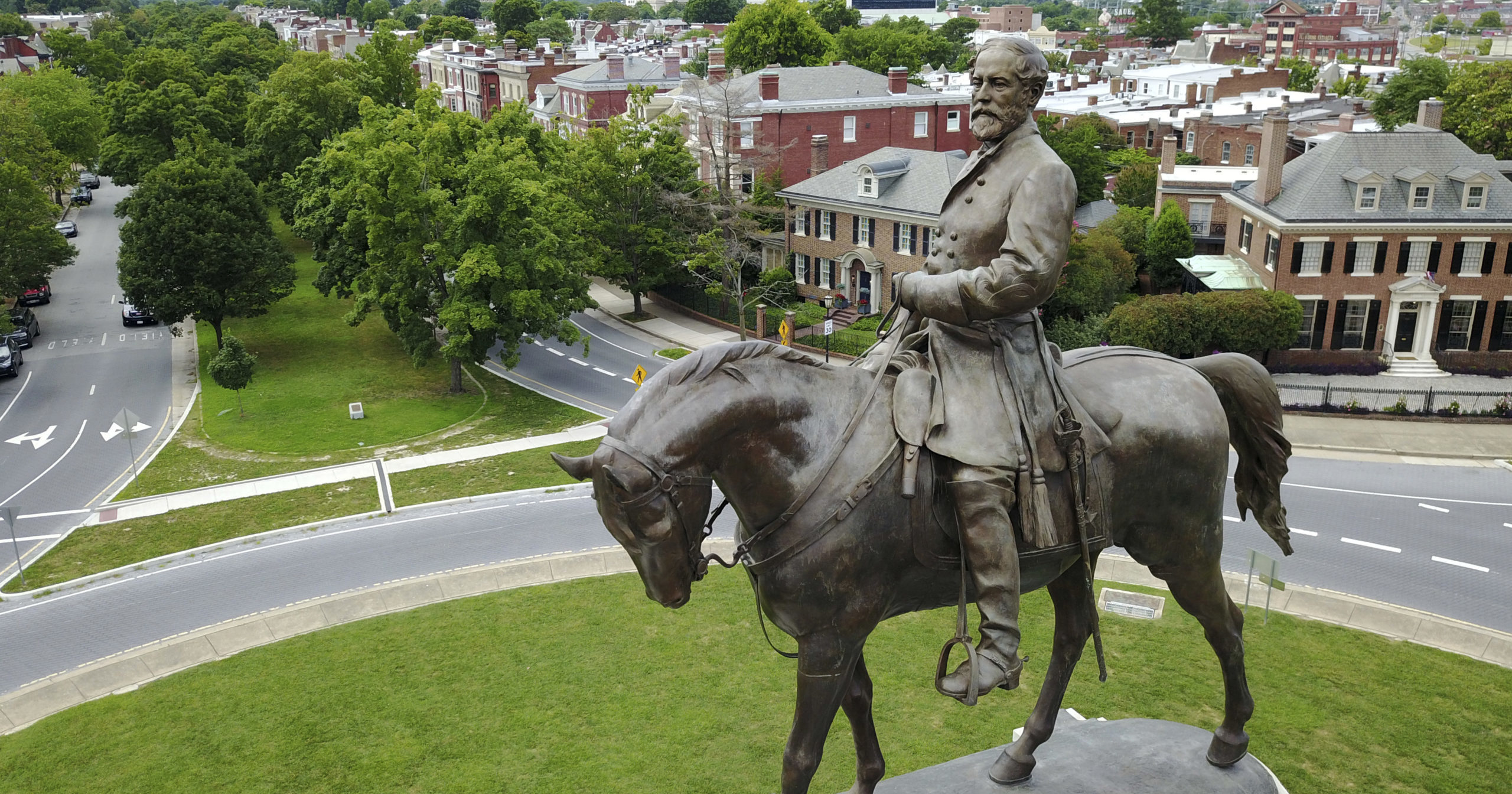 This June 27, 2017, file photo shows the statue of Confederate General Robert E. Lee that stands in the middle of a traffic circle on Monument Avenue in Richmond, Virginia. A lawsuit seeking to prevent Virginia Gov. Ralph Northam's administration from removing the statue can proceed, a judge ruled on Aug. 25, 2020.