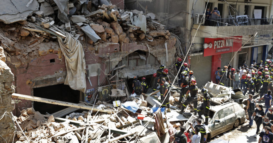 French and Lebanese firemen search in the rubble of a destroyed building after an explosion at the seaport in Beirut, Lebanon, on Aug. 6, 2020.