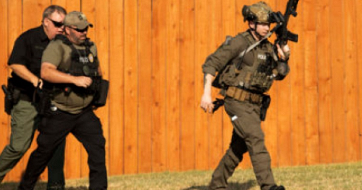 Police officers take up their stationsnear a house in Cedar Park, Texas, on Sunday during a hostage situation that left three officers wounded.