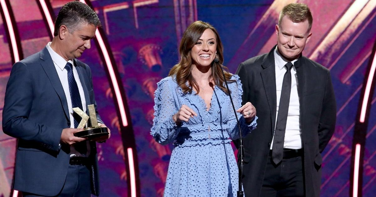 """Ashley Bratcher, center, along with Daryl Lefever, left, and Joe Knopp, accepts the Film Impact award for """"Unplanned"""" during the K-LOVE Fan Awards at the Grand Ole Opry House in Nashville, Tennessee, on June 2, 2019."""