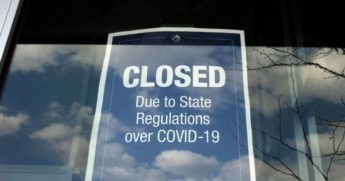 In this April 22, 2020, photo, a closed sign is posted in the window of a store because of the coronavirus at an outdoor mall, in Dedham, Massachusetts.