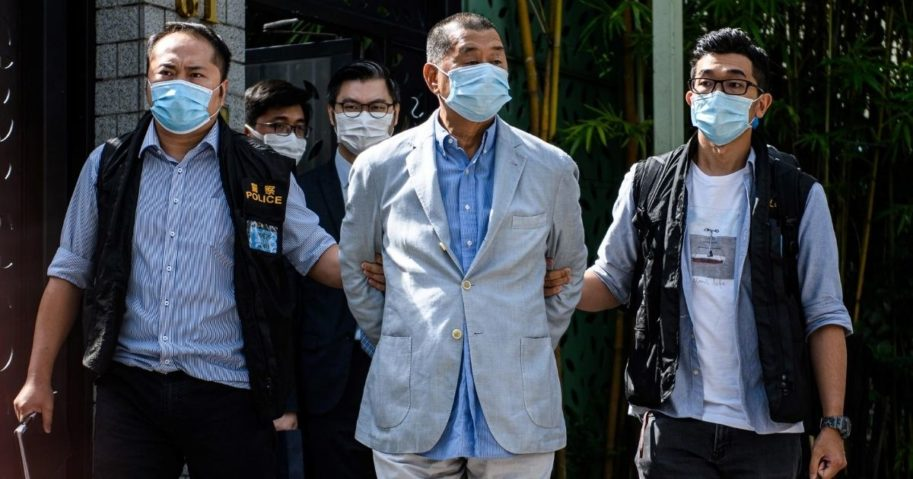 Police lead pro-democracy media mogul Jimmy Lai away from his home in Hong Kong on Aug. 10, 2020.