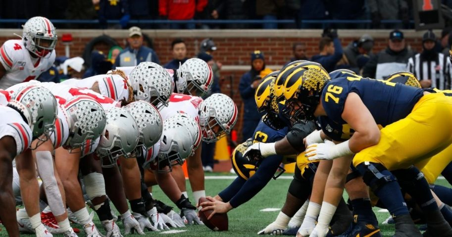 Ohio State and Michigan players play at the line of scrimmage in the first half of an NCAA college football game in Ann Arbor, Michigan, on Nov. 30, 2019.