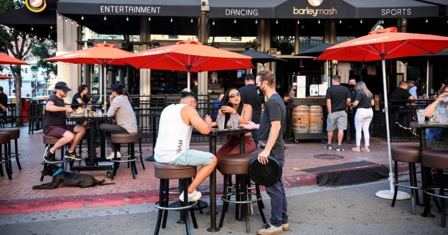 A waiter serves patrons at an outdoor restaurant along Fifth Avenue in the Gaslamp Quarter of downtown San Diego on July 17, 2020.