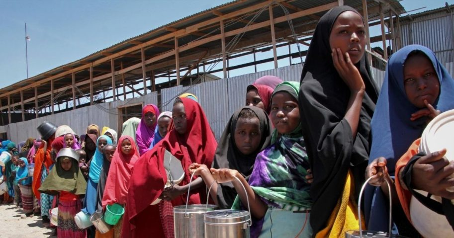 In this photo taken Saturday, Feb. 25, 2017, displaced Somali girls who fled the drought in southern Somalia stand in a queue to receive food handouts at a feeding center in a camp in Mogadishu, Somalia.