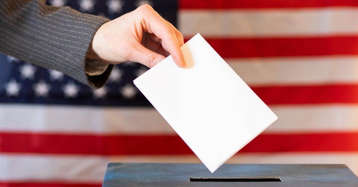 A stock image of a woman placing her ballot in a ballot box is pictured above.