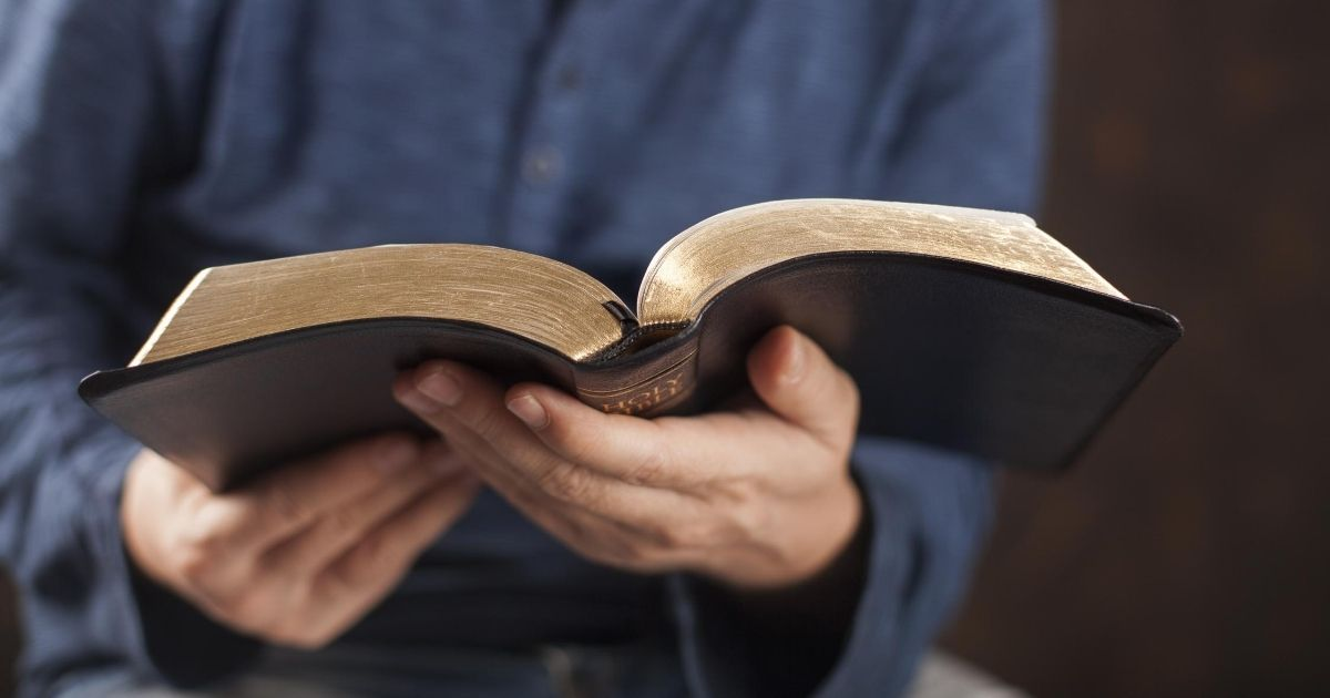 A stock image of a man reading the Bible is pictured above.