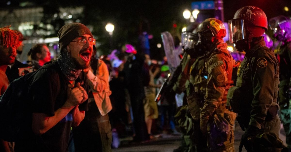A protester screams at federal officers in front of the Mark O. Hatfield U.S. Courthouse in the early hours of July 30, 2020, in Portland, Oregon.