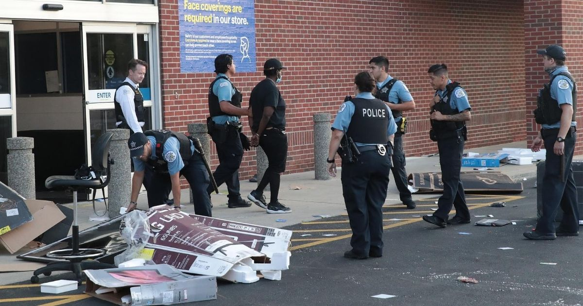 Police officers detain a man who was found inside of a Best Buy store after parts of the city had widespread looting and vandalism on Aug. 10, 2020, in Chicago.