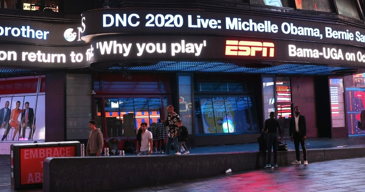 """An announcement for the Democratic National Convention is displayed Monday night on the ABC News' """"Good Morning America"""" as a handful of pedestrians pass by."""