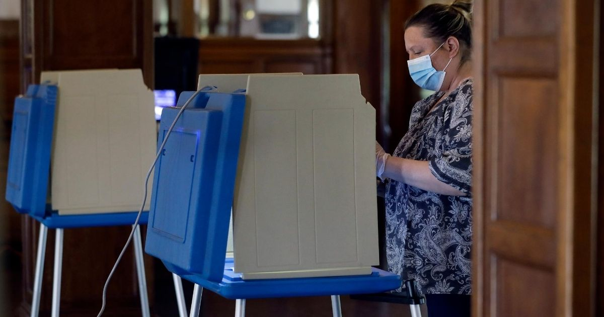 A voter stands at a voting booth on June 2, 2020, at a voting station in Providence, Rhode Island.