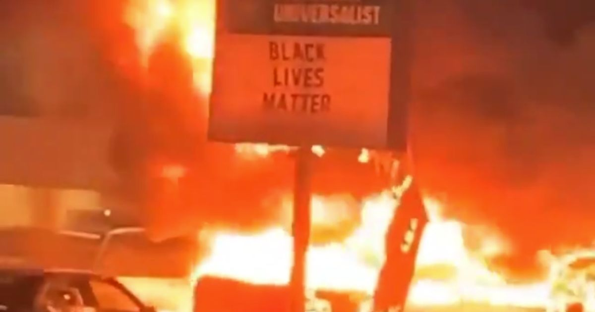 A sign at Bradford Community Church burns next to a used-car dealership in Kenosha, Wisconsin.