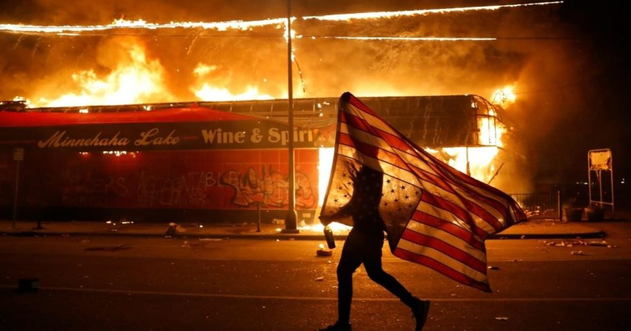 A protester carries a U.S. flag upside down, a sign of distress, next to a burning building during a May 28 riot in Minneapolis over the death of George Floyd.