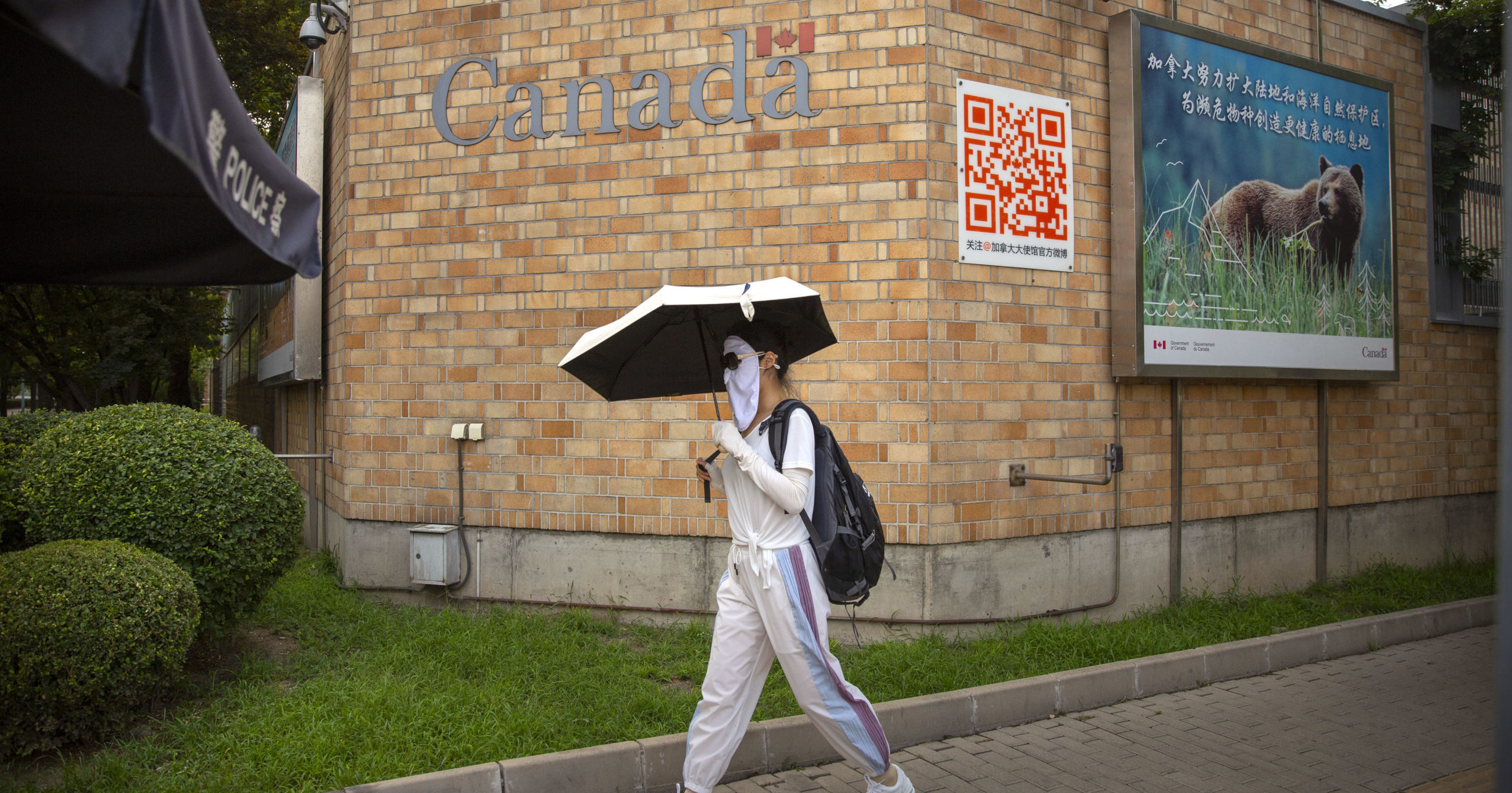 A woman wearing a face mask walks past the Canadian Embassy in Beijing on Aug. 6, 2020. China has sentenced a Canadian citizen to death on charges of manufacturing the drug ketamine amid heightened tension between the two countries.