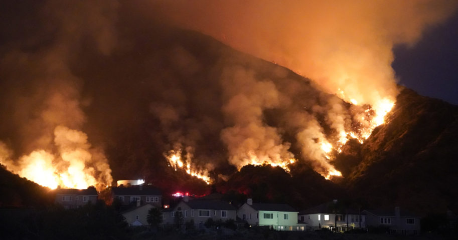 A fire burns through a residential area on Aug. 13, 2020, in Azusa, California. Heat wave conditions were making difficult work for fire crews battling wildfires across Southern California.