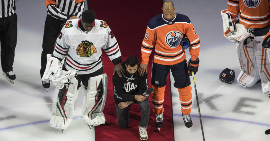 The Minnesota Wild's Matt Dumba takes a knee during the national anthem flanked by the Edmonton Oilers' Darnell Nurse, right, and the Chicago Blackhawks' Malcolm Subban before an NHL hockey game in Edmonton, Alberta on Aug. 1, 2020.