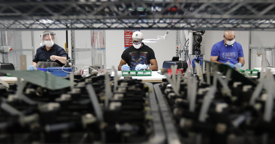 In this May 13, 2020, file photo, line workers put together ventilators at the Ford plant in Ypsilanti Township, Michigan. American industry rebounded last month as factories began to reopen.