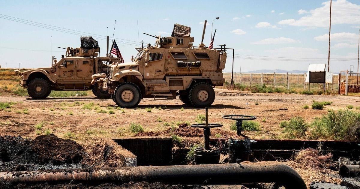 American soldiers drive past an oil field in Syria's northeastern Hasakeh province near the Turkish border on Aug. 4, 2020.