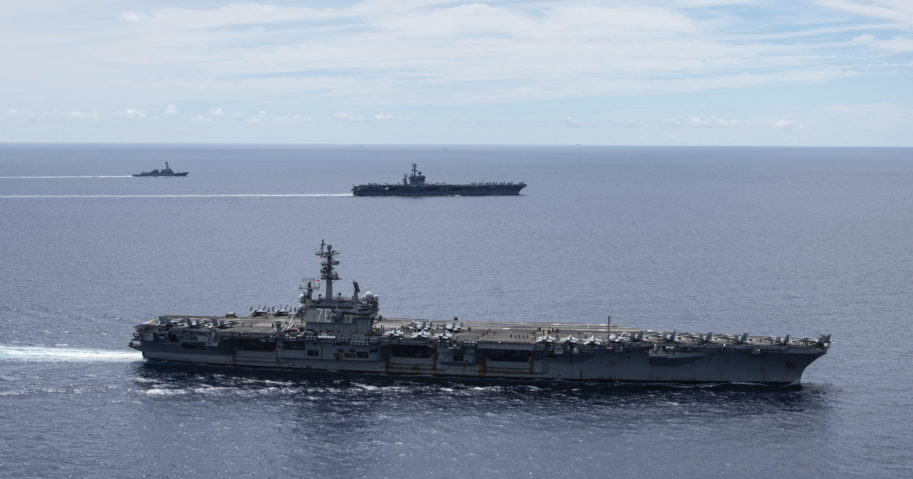 In this July 6, 2020, file photo provided by U.S. Navy, the USS Ronald Reagan and USS Nimitz sail together in formation in the South China Sea.
