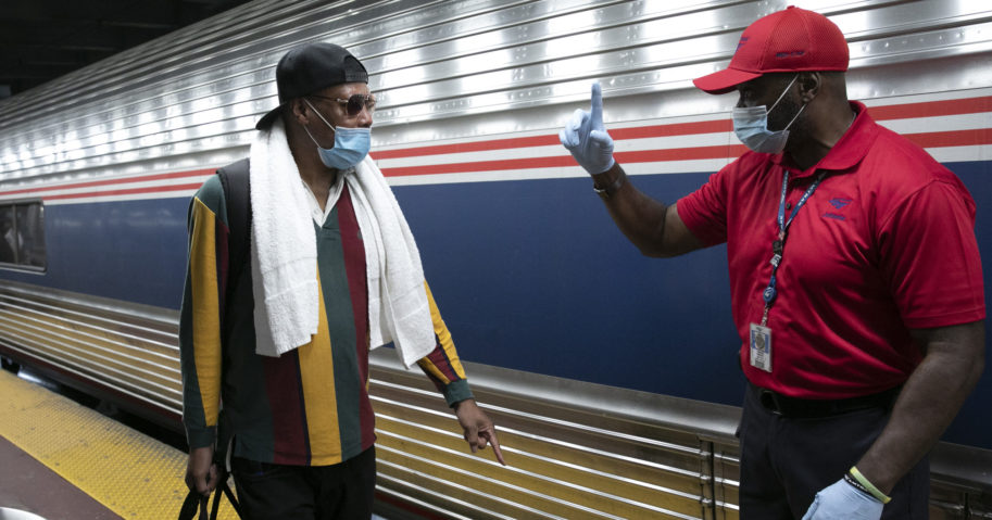 A traveler arriving on a train from Miami gets directions from a porter at Amtrak's Penn Station on Aug. 6, 2020, in New York. Mayor Bill de Blasio is ordering travelers from 34 states where COVID-19 infection rates are high to quarantine for 14 days upon arriving in the city.