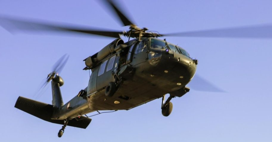 A UH-60 military helicopter flies in this stock image.