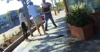Two men and a woman scuffle on the sidewal in Manhattan Beach, California.