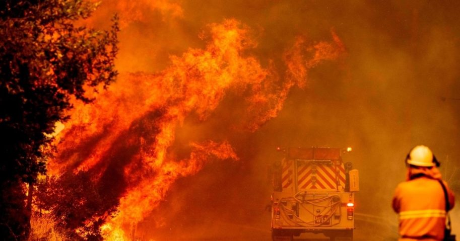 A fire truck drives through flames as a fire rages out of control near Lake Berryessa in Napa, California, on August 18, 2020.
