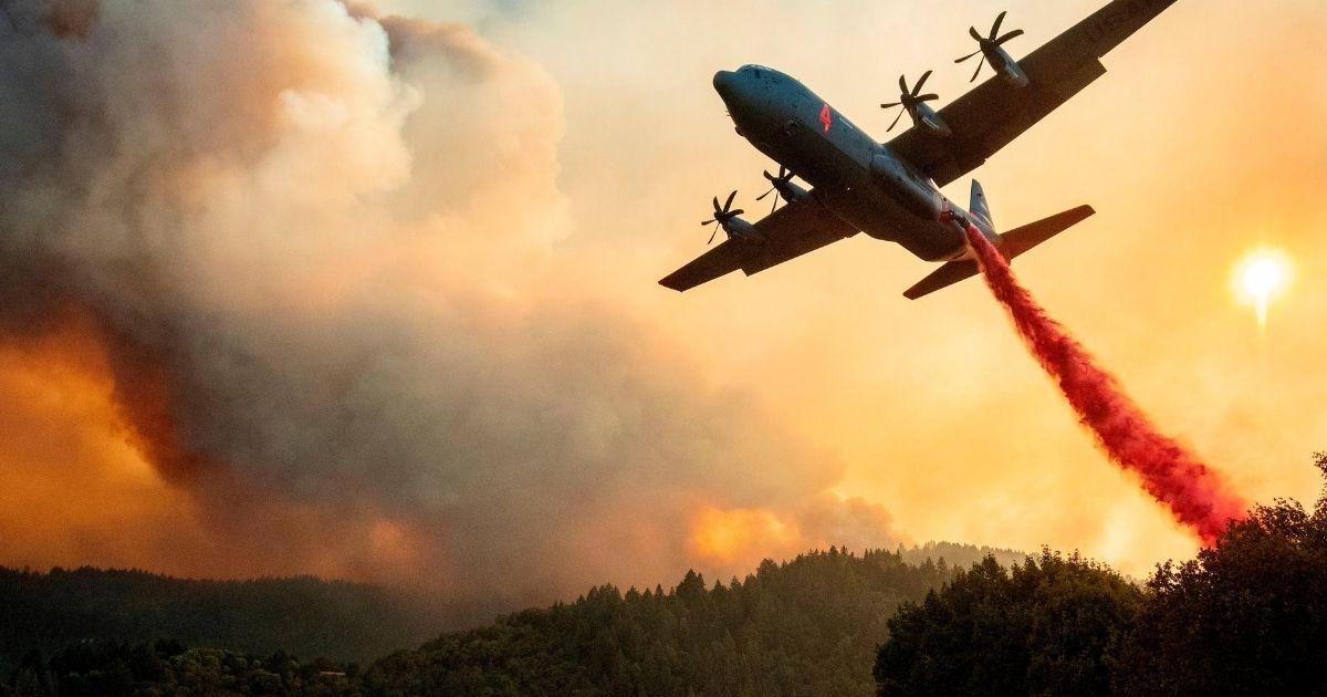 An aircraft drops fire retardant on a ridge as flames continue to spread in Healdsburg, California, on Aug. 20, 2020.