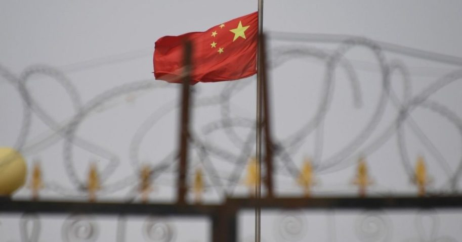 This photo taken on June 4, 2019, shows the Chinese flag behind razor wire at a housing compound in Yangisar in China's western Xinjiang region.