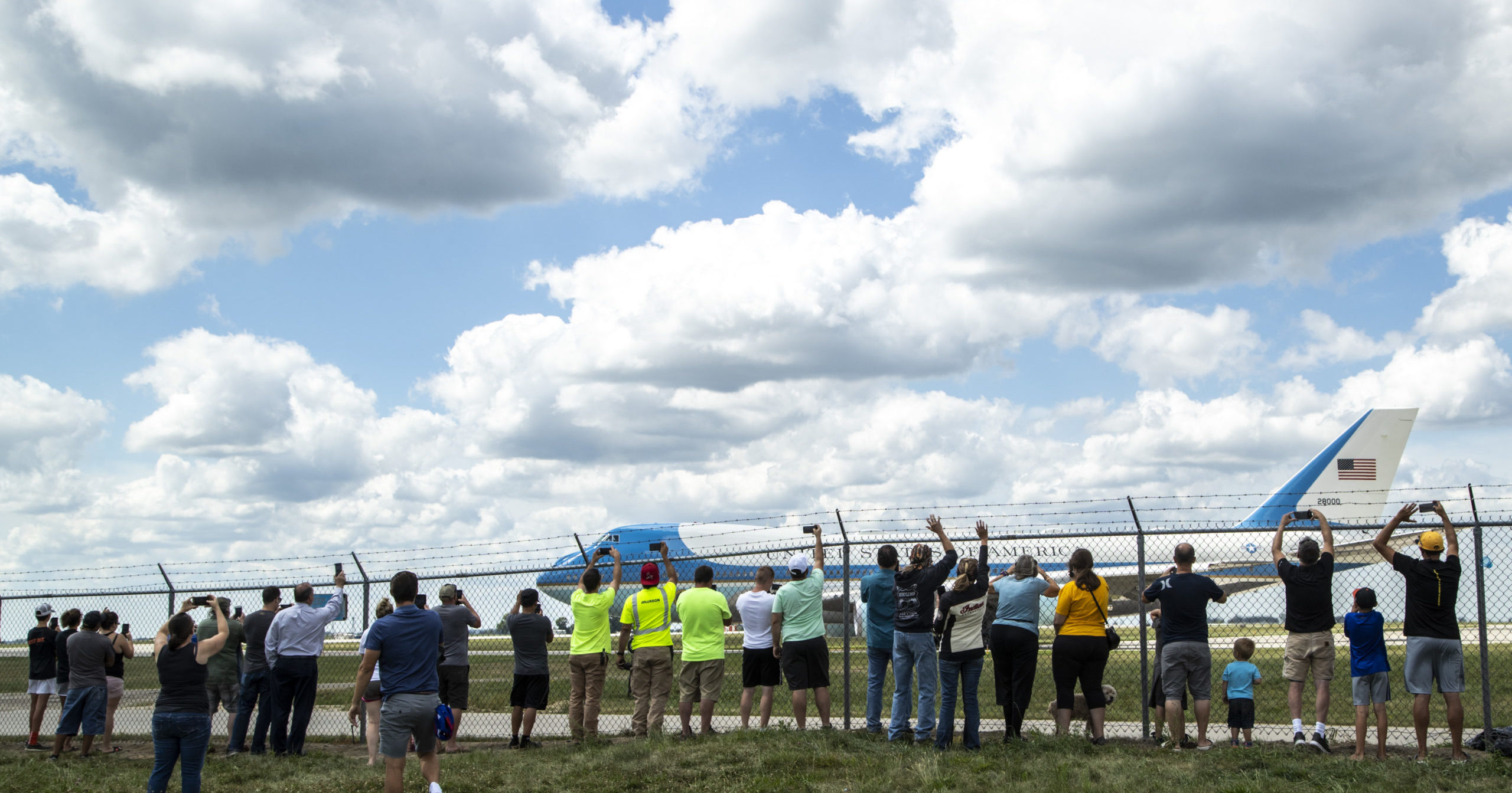 People lean up against a fence as Air Force One takes off on Aug. 18, 2020, after President Donald Trump visited with Iowa leaders in Cedar Rapids, Iowa. Trump attended a disaster recovery briefing at the airport in Cedar Rapids, one of the cities hit hardest by the Aug. 10 derecho that caused extensive damage to electricity infrastructure, homes and farms.