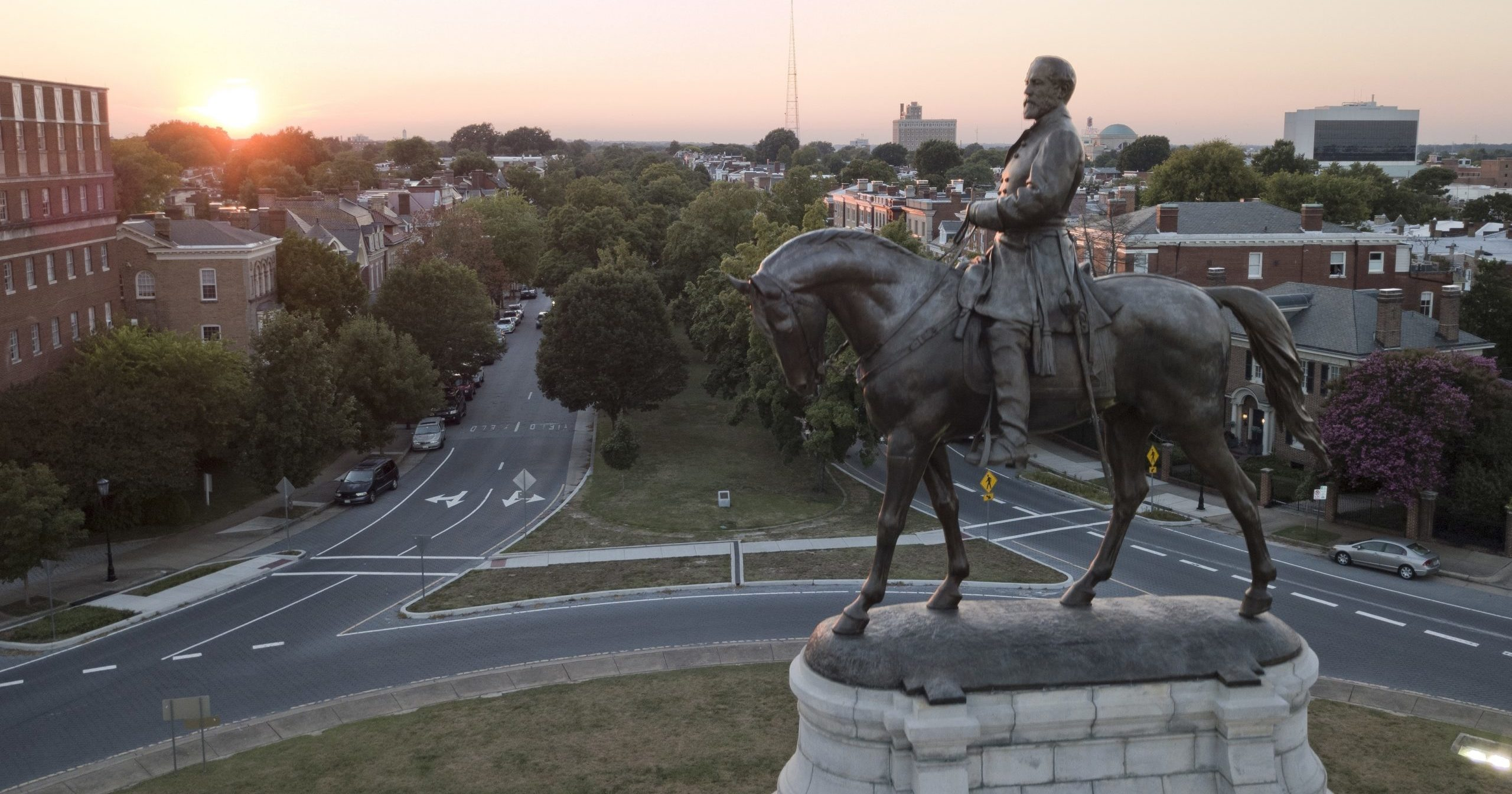 The sun sets behind the statue of confederate General Robert E. Lee on Monument Avenue in Richmond, Virginia, on July 31, 2017.