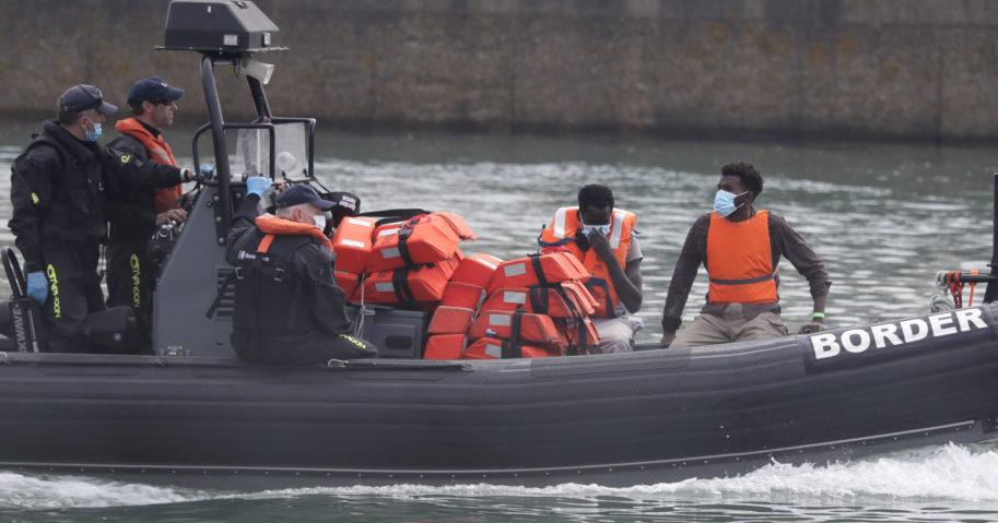 A Border Force vessel brings a group of people thought to be migrants into the port city of Dover, England, on Aug. 8, 2020. The British government says it will strengthen border measures as calm summer weather has prompted a record number of people to attempt the risky sea crossing from northern France to England.