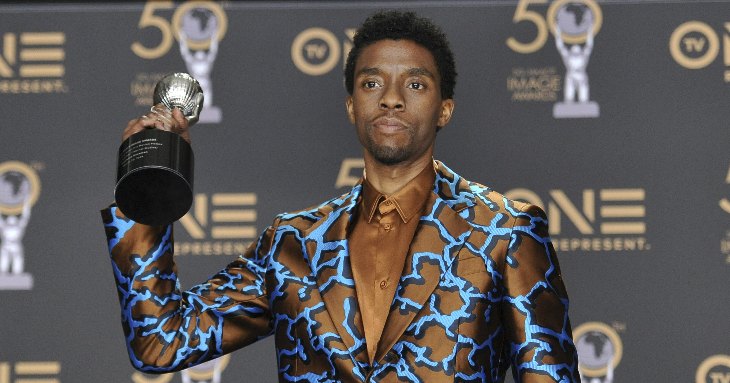 """In this March 30, 2019, file photo, Chadwick Boseman poses in the media room with the award for outstanding actor in a motion picture for """"Black Panther"""" at the 50th annual NAACP Image Awards at the Dolby Theatre in Los Angeles."""
