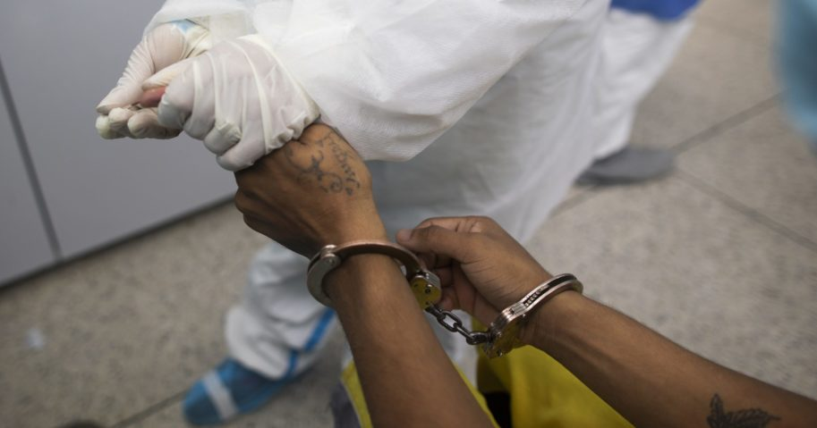 A doctor takes a blood sample for a COVID-19 test from a handcuffed inmate at a diagnosis center in Caracas, Venezuela, on Aug. 27, 2020.