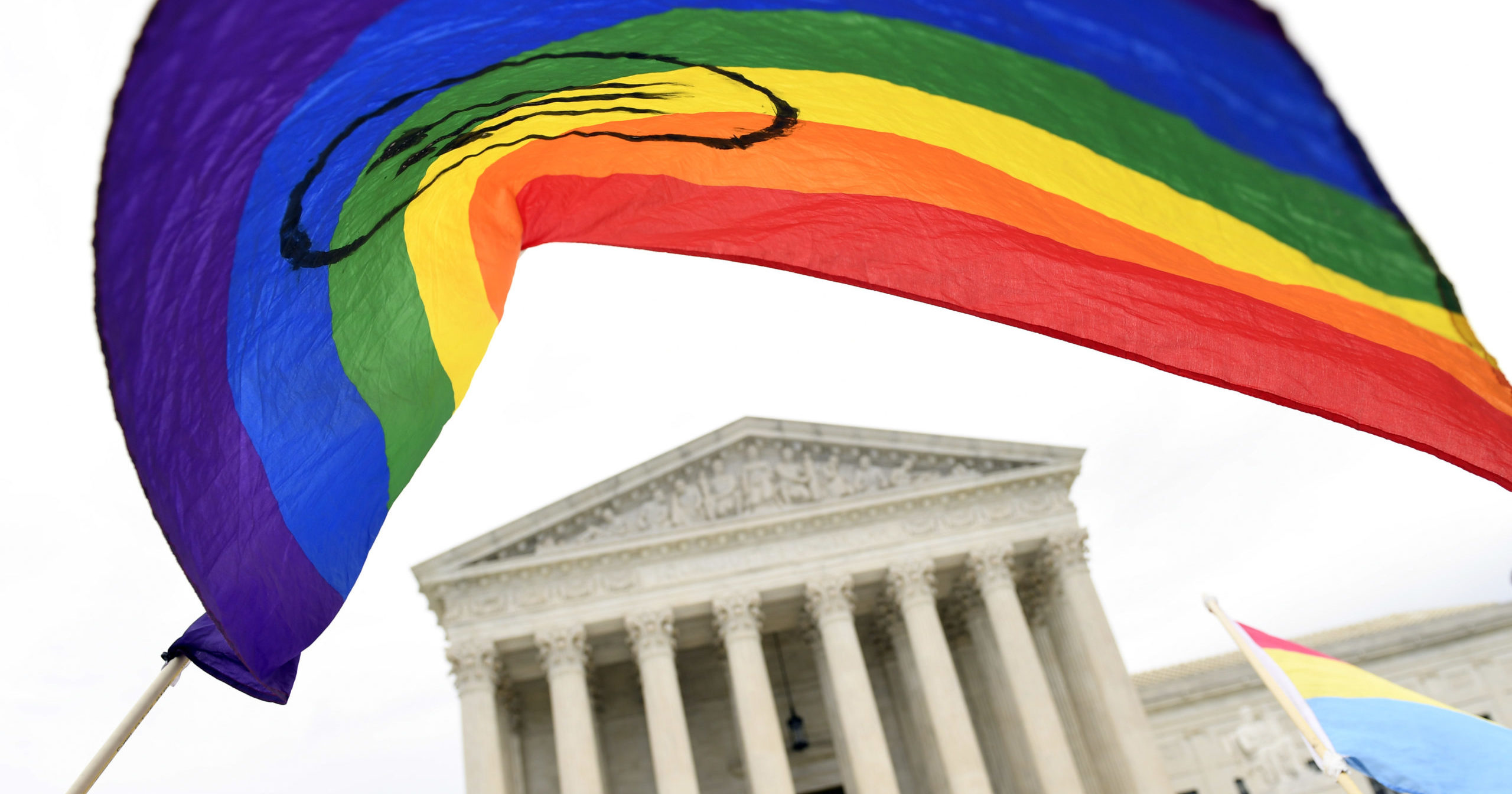 In this Oct. 8, 2019, file photo, the LGBT flag is waved outside the Supreme Court in Washington, D.C.