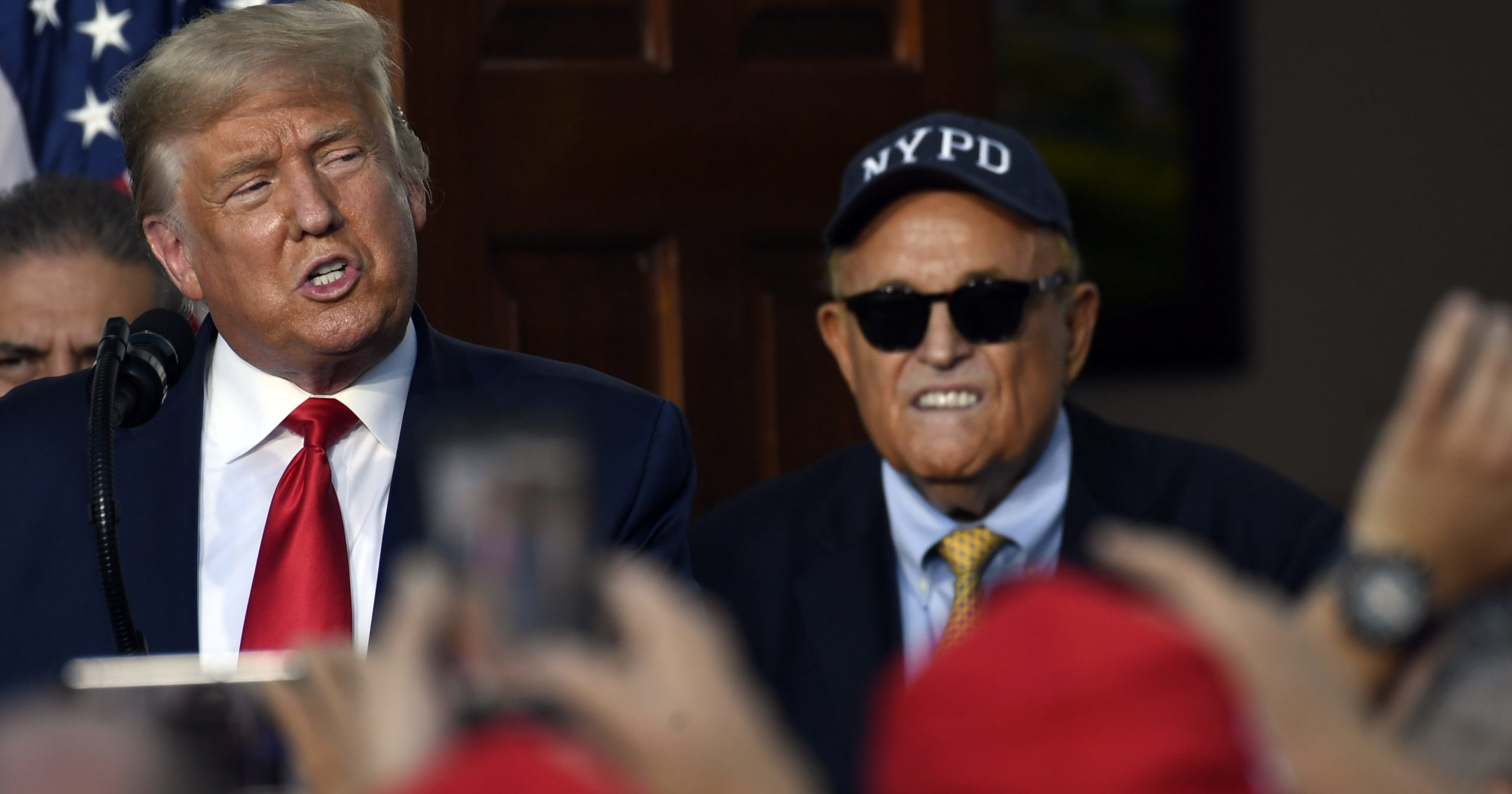 President Donald Trump speaks as Rudy Giuliani, an attorney for Trump, watches during an event at Trump National Golf Club on Aug. 14, 2020, in Bedminster, New Jersey, with members of the City of New York Police Department Benevolent Association.
