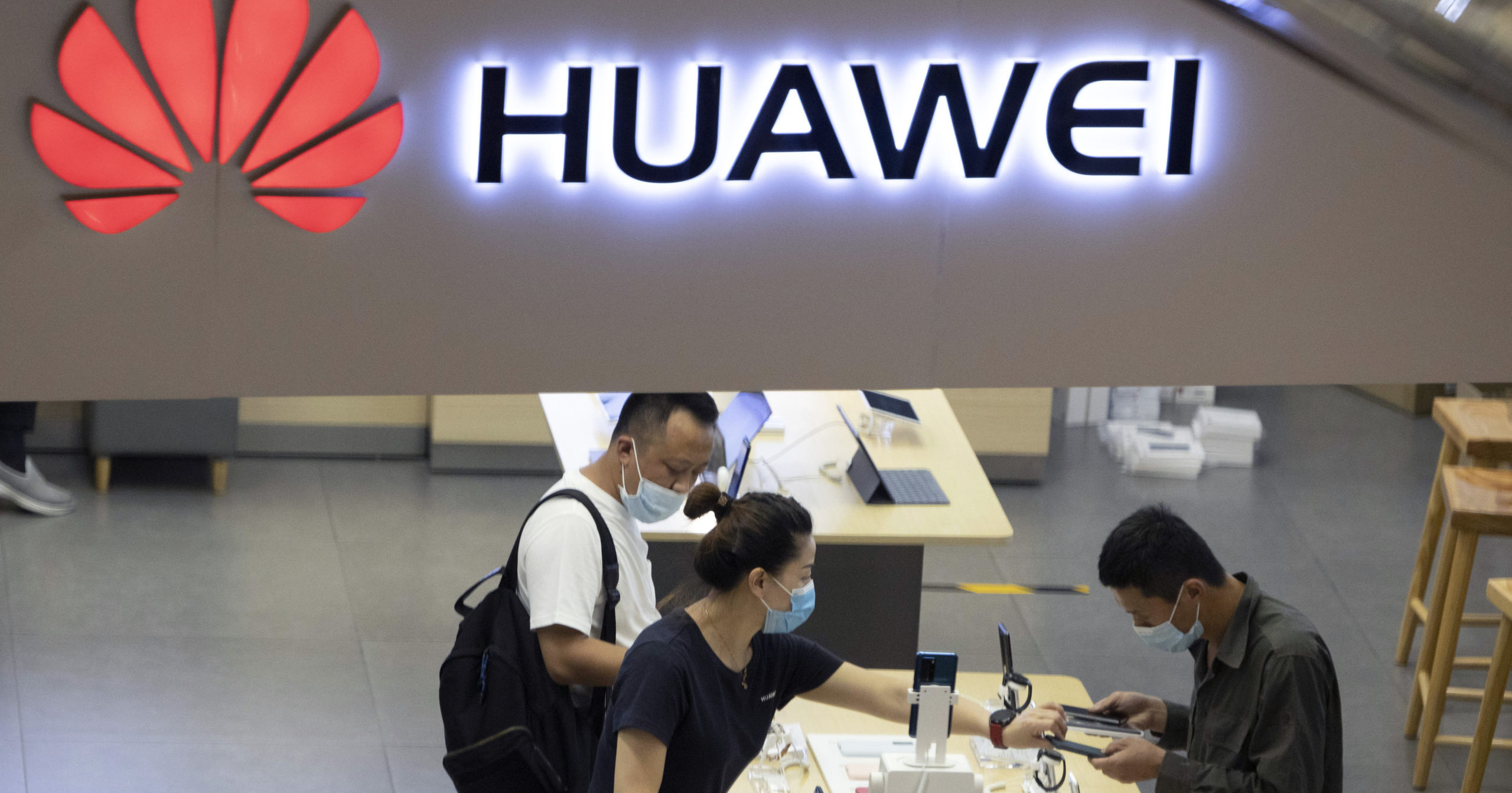 In this July 15, 2020, file photo, visitors wearing masks look at the latest products at a Huawei store in Beijing.