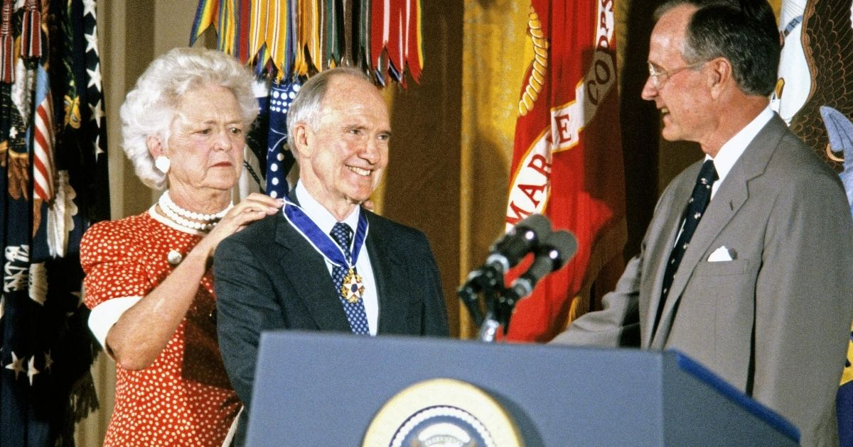 First Lady Barbara Bush fastens the Presidential Medal of Freedom around the neck of national security adviser Brent Scowcroft as he shakes hands with President George H.W. Bush during a ceremony in the White House's East Room in Washington, D.C., on July 3, 1991.