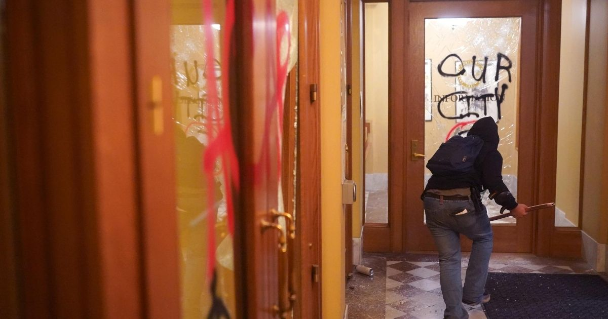 A rioter runs through the vandalized lobby of Portland City Hall as police announce an unlawful assembly outside on Aug. 25, 2020, in Portland, Oregon.