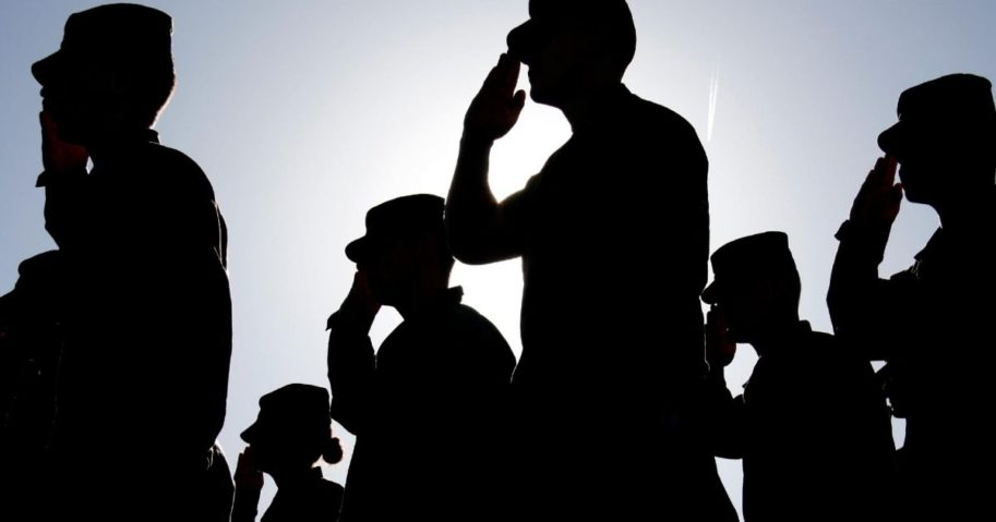 Saluting soldiers are seen in this stock image.
