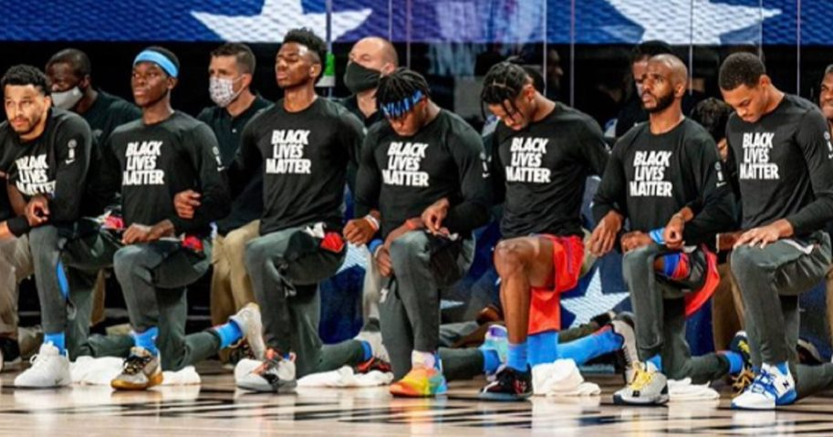 "Players for the Oklahoma City Thunder kneel during ""The Star-Spangled Banner."""